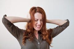 Μακρυμάλλης όμορφη νέα γυναίκα brunette που καλύπτει τα αυτιά της με τα χέρια της Στοκ Φωτογραφία