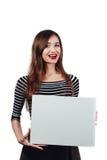 Μακρυμάλλης όμορφη χαριτωμένη γυναίκα brunette που κρατά μια ορθογώνια κενός-αφίσα άσπρος καμβάς με το διάστημα για το κείμενο χε Στοκ φωτογραφία με δικαίωμα ελεύθερης χρήσης