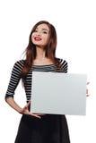 Μακρυμάλλης όμορφη χαριτωμένη γυναίκα brunette που κρατά μια ορθογώνια κενός-αφίσα άσπρος καμβάς με το διάστημα για το κείμενο χε Στοκ Εικόνες