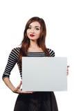 Μακρυμάλλης όμορφη χαριτωμένη γυναίκα brunette που κρατά μια ορθογώνια κενός-αφίσα άσπρος καμβάς με το διάστημα για το κείμενο χε Στοκ Φωτογραφίες