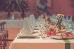 Μακρύς εξυπηρετούμενος πίνακας με τα πιάτα στοκ φωτογραφίες