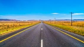 Μακρύς ευθύς δρόμος μέσω του ατελείωτου ευρέος ανοικτού τοπίου της ημι περιοχής Karoo ερήμων στο ελεύθερο κράτος και την ανατολικ Στοκ Εικόνες