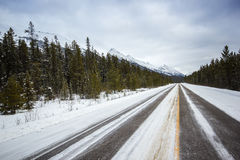 Μακρύς κενός χειμερινός δρόμος που οδηγεί στα βουνά, εθνικό πάρκο Banff, Καναδάς Στοκ Φωτογραφίες