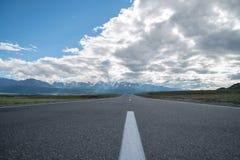 μακρύς δρόμος ασφάλτου Βουνά στον ορίζοντα στοκ εικόνα