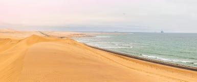 Μακρύς δρόμος στους αμμόλοφους της ερήμου της Καλαχάρης με την ατλαντική παραλία, Στοκ Φωτογραφία