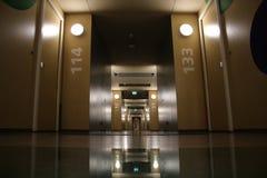 Μακρύς τεντωμένος διάδρομος με τα διαμερίσματα, τις μικρά λάμπες φωτός και το γυαλί στο πάτωμα στοκ φωτογραφία με δικαίωμα ελεύθερης χρήσης