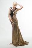 Μακρύ φόρεμα μόδας ομορφιάς γυναικών, κομψό κορίτσι στη χρυσή εσθήτα Στοκ Φωτογραφίες