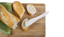 Μακρύ baguette και ξύλινο βουτύρου μαχαίρι στον ξύλινο τέμνοντα πίνακα Στοκ Εικόνα