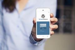 ΜΑΛΑΓΑ, ΙΣΠΑΝΙΑ - 26 ΑΠΡΙΛΊΟΥ 2015: Χέρι γυναικών που παρουσιάζει κινητό τηλέφωνο με τη σελίδα σύνδεσης Wordpress στην οθόνη Το W Στοκ φωτογραφίες με δικαίωμα ελεύθερης χρήσης