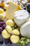 Μαλακά και σκληρά τυριά με τα σταφύλια στοκ εικόνα