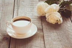 Μαλακά πλήρη φγμένα άσπρα τριαντάφυλλα με το φλυτζάνι του μαύρου καφέ στον ξύλινο πίνακα με το διάστημα αντιγράφων εικόνα που τον στοκ εικόνα
