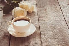 Μαλακά πλήρη φγμένα άσπρα τριαντάφυλλα με το φλυτζάνι του μαύρου καφέ στον ξύλινο πίνακα με το διάστημα αντιγράφων εικόνα που τον στοκ εικόνα με δικαίωμα ελεύθερης χρήσης