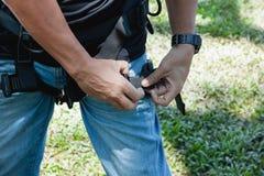 Μαλακή ασιατική ένδυση νεαρών άνδρων εστίασης στενή επάνω το λουρί ασφάλειας στοκ εικόνα
