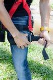 Μαλακή ασιατική ένδυση νεαρών άνδρων εστίασης στενή επάνω το λουρί ασφάλειας για την εργασία στο ύψος στοκ εικόνες
