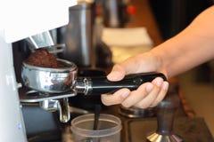 Μαλακή εκμετάλλευση barista γυναικών εστίασης ασιατική portafilter για τη φρέσκια έκχυση καφέ έξω μιας μηχανής μύλων καφέ στοκ εικόνα