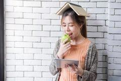 Μαλακή εστίαση της ευτυχούς και υγιούς νέας γυναίκας με το βιβλίο στο κεφάλι, Ε Στοκ εικόνα με δικαίωμα ελεύθερης χρήσης