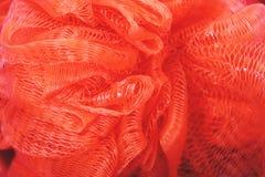 Μαλακό κόκκινο σφουγγάρι για το λουτρό και το ντους, το υπόβαθρο και τη σύσταση στοκ εικόνα