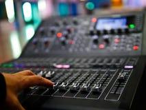 Μαλακό χέρι εστίασης που ρυθμίζει τον επαγγελματικό ψηφιακό ακουστικό ελεγκτή αναμικτών στο θάλαμο ελέγχου, υγιής έλεγχος αναμικτ Στοκ Εικόνα