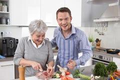 Μαμά ξενοδοχείων: νεαρός άνδρας και ηλικιωμένη γυναίκα που μαγειρεύουν μαζί το χοιρινό κρέας Στοκ φωτογραφία με δικαίωμα ελεύθερης χρήσης