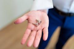 Μανικετόκουμπα στο χέρι των ατόμων Στοκ Φωτογραφία