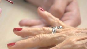 Μανικιουρίστας που εφαρμόζει επαγγελματικά το βερνίκι στα καρφιά απόθεμα βίντεο