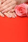 Μανικιούρ. Θηλυκά χέρια στην κόκκινη ανασκόπηση Στοκ φωτογραφία με δικαίωμα ελεύθερης χρήσης