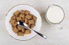 Μαξιλάρια δημητριακών, κουταλάκι του γλυκού στο κύπελλο, κανάτα του γάλακτος στον πίνακα Στοκ Εικόνες