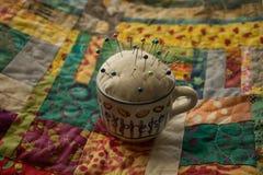 Μαξιλάρι καρφιτσών φλυτζανιών τσαγιού στο ζωηρόχρωμο πάπλωμα Στοκ Εικόνες