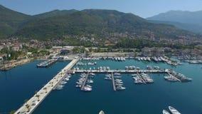 Μαρίνα πολυτέλειας του Πόρτο Μαυροβούνιο με τα άσπρα γιοτ, τις πλέοντας βάρκες και το κρουαζιερόπλοιο απόθεμα βίντεο