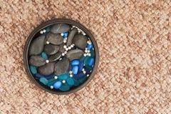Μαργαριτάρια και χρωματισμένες πέτρες στο βάζο αργίλου στο υπόβαθρο ταπήτων Στοκ Εικόνες