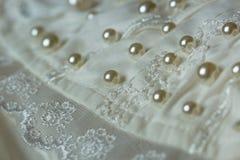 Μαργαριτάρια που κεντιούνται μικροσκοπικά πέρα από ένα γαμήλιο φόρεμα στοκ φωτογραφία