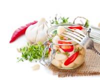 Μαριναρισμένο σκόρδο με τα μικτά τσίλι και τα χορτάρια στο βάζο γυαλιού Στοκ Φωτογραφίες