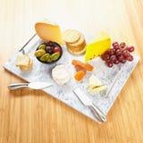 Μαρμάρινο εξυπηρετώντας πιάτο με το τυρί και τις κροτίδες, ελιές, σταφύλια, βερίκοκα, μαχαίρια τυριών Στοκ Εικόνες