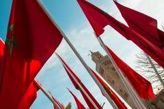 Μαροκινές σημαίες στο Μαρακές σε ένα υπόβαθρο του μουσουλμανικού τεμένους και του μπλε ουρανού Koutoubia Στοκ Εικόνα