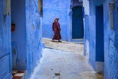 Μαροκινή γυναίκα που περπατά σε μια στενή οδό στην πόλη Chefchaouen στο Μαρόκο Στοκ φωτογραφία με δικαίωμα ελεύθερης χρήσης