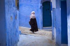 Μαροκινή γυναίκα που περπατά σε μια στενή οδό στην πόλη Chefchaouen στο Μαρόκο, Βόρεια Αφρική Στοκ εικόνα με δικαίωμα ελεύθερης χρήσης