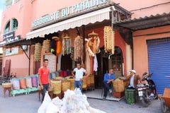 Μαροκινή πόλη - δύο νέα στάση αγοριών και δύο παλαιότεροι τύποι που κάθονται μπροστά από ένα κατάστημα, δίπλα στα κρεμασμένα αγαθ στοκ φωτογραφία