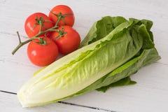 Μαρούλι και ντομάτες σε έναν λευκό πίνακα στοκ φωτογραφία