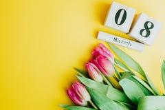 8 Μαρτίου ευτυχής έννοια ημέρας γυναικών ` s Με το ξύλινο ημερολόγιο φραγμών και τις ρόδινες τουλίπες στο κίτρινο υπόβαθρο διάστη στοκ εικόνες