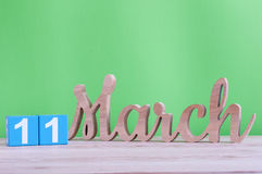 11 Μαρτίου Ημέρα 11 του μήνα, του καθημερινού ξύλινου ημερολογίου στον πίνακα και του πράσινου υποβάθρου Ημέρα άνοιξη, κενό διάστ Στοκ φωτογραφία με δικαίωμα ελεύθερης χρήσης