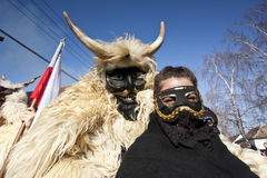 Μασκφόρος καρναβαλιού στη γούνα με ένα κορίτσι «Sokac» στο «Busojaras», το καρναβάλι της χειμερινής κηδείας Στοκ Εικόνες