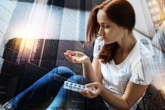 Ματαιωμένη γυναίκα που εξετάζει τα χάπια στο χέρι της και που αισθάνεται κακή Στοκ φωτογραφίες με δικαίωμα ελεύθερης χρήσης
