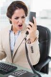 Ματαιωμένη επιχειρηματίας που φωνάζει στο τηλέφωνο Στοκ Εικόνες