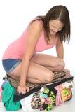 Ματαιωμένη τονισμένηη νέα γυναίκα που προσπαθεί να κλείσει μια ξεχειλίζοντας βαλίτσα με την ικεσία σε το στοκ εικόνα