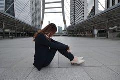 Ματαιωμένη τονισμένη νέα ασιατική επιχειρησιακή γυναίκα που κάθεται και που αγκαλιάζει τα γόνατά του μέχρι το στήθος στο πάτωμα σ Στοκ Εικόνες
