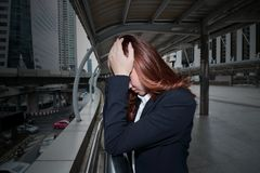 Ματαιωμένη τονισμένη νέα ασιατική επιχειρησιακή γυναίκα που καλύπτει το πρόσωπο με τα χέρια στο αστικό υπόβαθρο πόλεων στοκ φωτογραφία