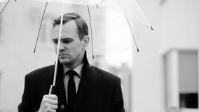 Ματαιωμένος από τον καιρό, που στέκεται κάτω από την ομπρέλα κατά τη διάρκεια της βροχής Δυστυχισμένο άτομο σε ένα κοστούμι απόθεμα βίντεο
