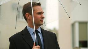 Ματαιωμένος από τον καιρό, που στέκεται κάτω από την ομπρέλα κατά τη διάρκεια της βροχής Δυστυχισμένο άτομο σε ένα κοστούμι φιλμ μικρού μήκους