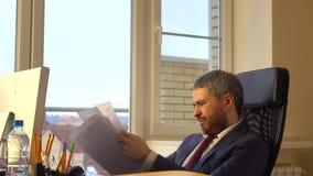 Ματαιωμένος γενειοφόρος επιχειρηματίας που ρίχνει το τσαλακωμένο επιχειρησιακό έγγραφο μακριά απόθεμα βίντεο