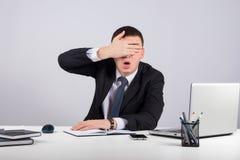 Ματαιωμένος επιχειρηματίας κοντά τα μάτια του με το χέρι στο γκρίζο υπόβαθρο Στοκ φωτογραφία με δικαίωμα ελεύθερης χρήσης